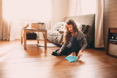 Kid girl helping with housework and cleaning wooden floor at home. Funny kid girl helping with housework and cleaning wooden floor at home royalty free stock photography