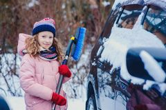 Kid girl helping to clean car from snow on winter backyard or parking. Car covered with snow after blizzard stock photos