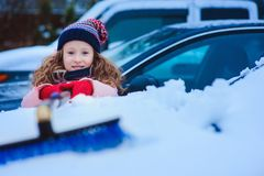 Kid girl helping to clean car from snow on winter backyard or parking. Car covered with snow after blizzard royalty free stock photos