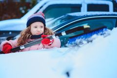 Kid girl helping to clean car from snow on winter backyard or parking stock images