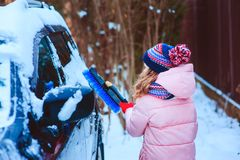 Kid girl helping to clean car from snow on winter backyard or parking stock photo
