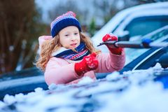 Kid girl helping to clean car from snow on winter backyard or parking royalty free stock photography