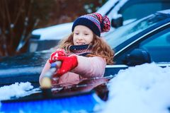 Kid girl helping to clean car from snow on winter backyard or parking. royalty free stock photography