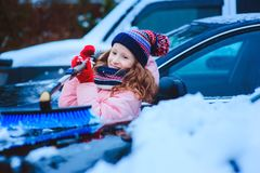 Kid girl helping to clean car from snow on winter backyard or parking. Car covered with snow after blizzard stock photography