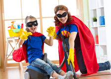 Kid girl and her mother weared Superhero costumes. Cute helper child and woman make cleaning room and have a fun. Royalty Free Stock Images