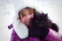 Kid girl holding black cat and smiling Royalty Free Stock Photos