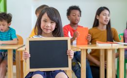 Kid girl holding blank blackboard with diversity friends and tea royalty free stock photo