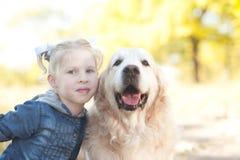 Kid girl holding dog outdoors. Closeup portrait of cute kid girl holding labrador outdoors Royalty Free Stock Photo