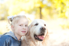 Kid girl holding dog outdoors. Closeup portrait of cute kid girl holding labrador outdoors Royalty Free Stock Images