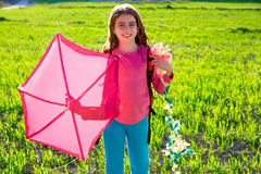 Kid girl holding pink kite in spring meadow Stock Photo