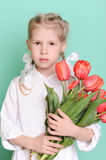 Kid girl holding red tulips Royalty Free Stock Images