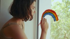 Kid girl at home on the window draws a rainbow during coronavirus Covid-19 the quarantine period on self-isolation. Stay