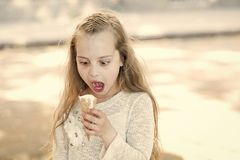 Kid girl with ice cream cone in hand. Summer treats concept. Sweet tooth girl child with white ice cream in waffle cone. Girl sweet tooth on shocked face eats royalty free stock image