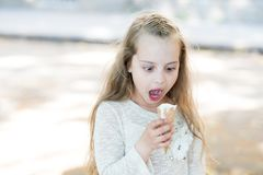 Kid girl with ice cream cone in hand. Summer treats concept. Sweet tooth girl child with white ice cream in waffle cone. Girl sweet tooth on shocked face eats Royalty Free Stock Photos
