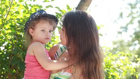 Kid girl kissing joying happy mother outdoors stock footage