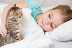 Kid girl with kitten laying in bed Royalty Free Stock Photos