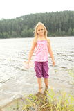 Kid - girl in a lake. Little kid - smiling girl standing in the water of lake and holding her shoes royalty free stock photography