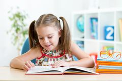 Kid girl learns to read book. Child girl learns to read sitting at table in nursery Royalty Free Stock Photo