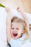 Kid girl lie on bed. Blonde girl stock photography