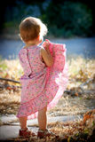 Kid girl lifting up her dress. And looking away royalty free stock photo