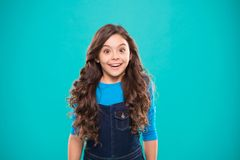 Kid girl long healthy shiny hair wear casual clothes. Little girl excited happy face. Kid happy cute face feels excited. Blue background. Sincere excitement stock photo