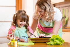 Kid girl with mom cooking fish in the kitchen. Smiling kid girl with mom cooking fish in domestic kitchen Stock Image