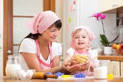 Kid girl with mom making dough in the kitchen. Kid girl with her mom making dough in the kitchen royalty free stock images