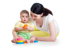 Kid girl and mom play together with cup toys. Kid girl and mom playing together with colorful toys Stock Photos