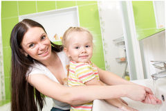 Kid girl with mom washing in bathroom. Smiling child with mom washing hands in bathroom Royalty Free Stock Image