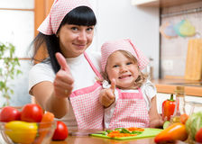 Kid girl and mother cooking and showing thumb up. Child girl and mother cooking and showing thumb up stock photo