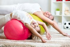 Kid girl and mother do gymnastic together indoors. Kid girl and mother doing gymnastic together indoors stock photography