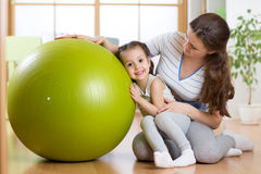 Kid girl and mother with fitness ball. Indoor Stock Photos