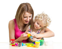 Kid girl and mother play colorful clay toy Stock Photos