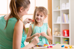 Kid girl and mother play colorful clay toys at Royalty Free Stock Photo