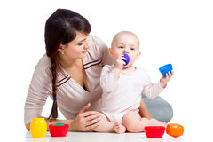 Kid girl and mother play together with cup toys Stock Images