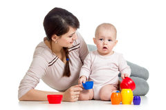 Kid girl and mother play together with cup toys Stock Photos