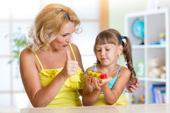 Kid girl and mother play together at home Royalty Free Stock Photography