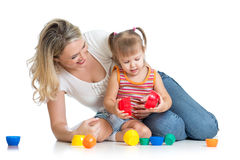 Kid girl and mother play together with toys. Kid girl and mother playing together with cup toys Royalty Free Stock Photography