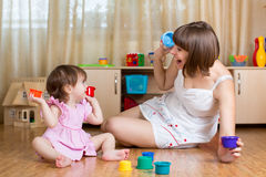 Kid girl and mother play together with toys Stock Images