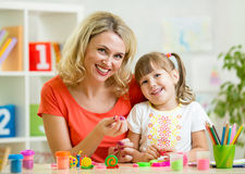 Kid girl and mother playing colorful clay toy Royalty Free Stock Photography