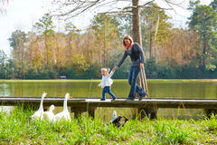 Kid girl and mother playing with ducks in lake Stock Image