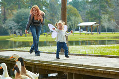 Kid girl and mother playing with ducks in lake Royalty Free Stock Images