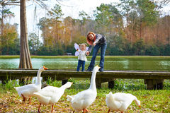 Kid girl and mother playing with ducks in lake Royalty Free Stock Photo