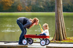 Kid girl and mother playing in lake with pull cart Royalty Free Stock Photos