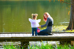 Kid girl and mother playing in the park lake Stock Photography