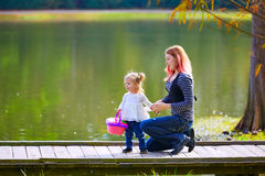 Kid girl and mother playing in the park lake Royalty Free Stock Photo