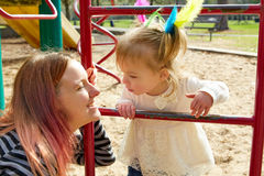 Kid girl and mother playing playground ladder Royalty Free Stock Images