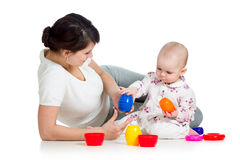 Kid girl and mother playing together with cup toys Stock Photography