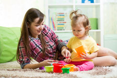 Kid girl and  mother playing together at home Stock Photo