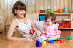 Kid girl and mother playing together with toys Stock Photography